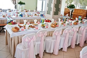 Chairs with pink bow at wedding hall