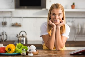 happy young woman in apron leaning a