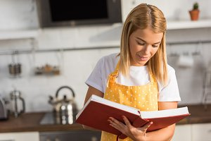 smiling young woman in apron reading