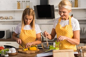 adult mother and daughter in aprons