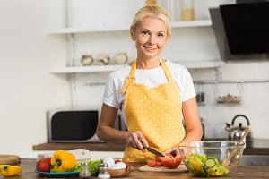 happy mature woman in apron smiling