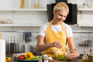 happy mature woman in apron cooking