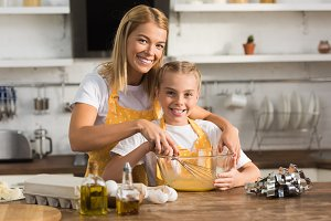 happy mother and daughter whisking e