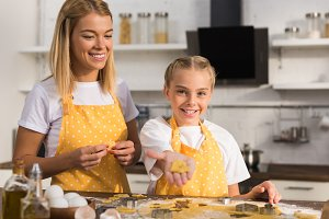 happy mother and daughter in aprons