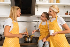 happy family in aprons smiling each