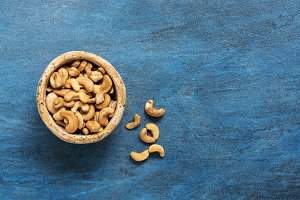 Bowl with cashew nuts on a blue