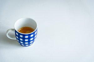 A cup of coffee with blue stripes