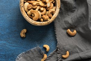 Roasted cashews in a bowl on a blue