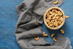A bowl of roasted cashews on a blue