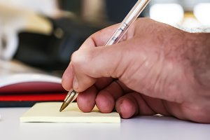 Male hand writing with pen
