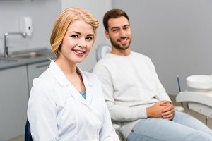 smiling female dentist and handsome