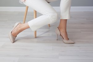 Women's legs in white trousers
