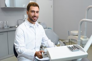 smiling young dentist in white coat