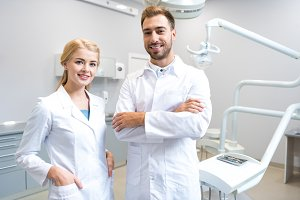 young male and female dentists looki
