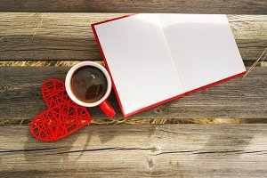 Red mug with coffee in wooden bench