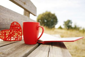 Red mug with coffee in a wooden benc