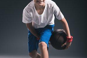 stylish boy playing basketball on gr