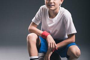 stylish boy sitting on basketball ba