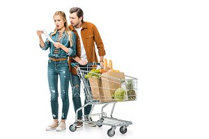 shocked couple with trolley full of