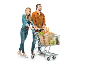 cheerful couple carrying shopping tr