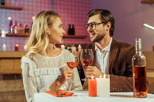smiling couple clinking by wine glas
