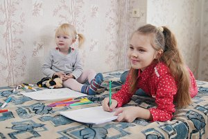 Two little girls lying on the bed