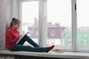 A little girl sitting on the window