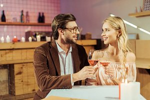 cheerful couple clinking by wine gla