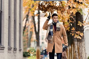 stylish man in coat with golden leav