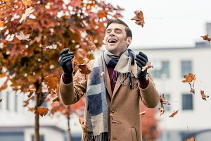 handsome happy man in coat and scarf