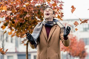 handsome laughing man in coat and sc