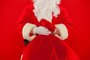 Santa Claus hand holding red sack