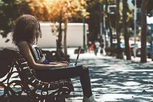 Charming lady with laptop on bench