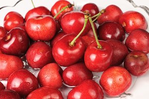 Red cherries in a dish of water