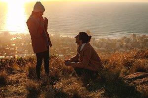 Man kneeling to female on cliff