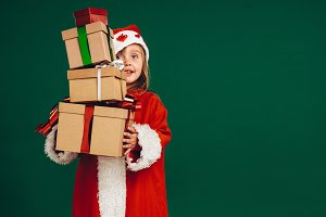 Kid in santa costume holding gift
