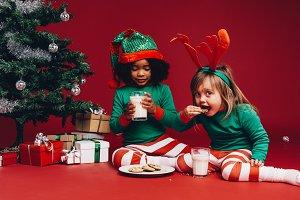 Little girls eating cookies sitting
