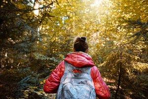 woman hiker in a red jacket walks in