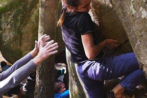 A woman rock climber climbing a rock