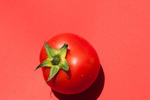 Red tomato on a red background