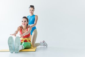 smiling sporty girls stretching and