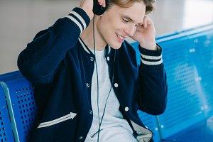 smiling young man in headphones sitt