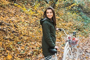 smiling young woman carrying bicycle