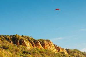One man gliding using a parachute