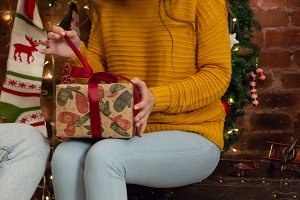 The girl in a yellow sweater unwraps