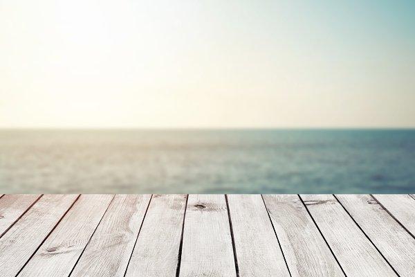wood table top on blur sea