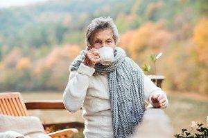 An elderly woman drinking coffee