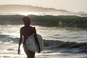 Surfing girl at sunset