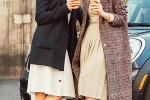happy stylish women in coats posing
