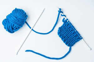top view of blue yarn and knitting n